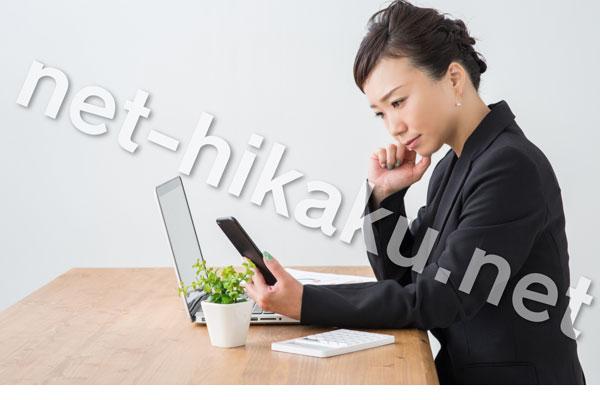 パソコンとスマホを見て悩むスーツの女性