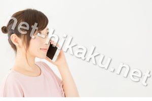 スマホで電話するピンクのTシャツを着た女性