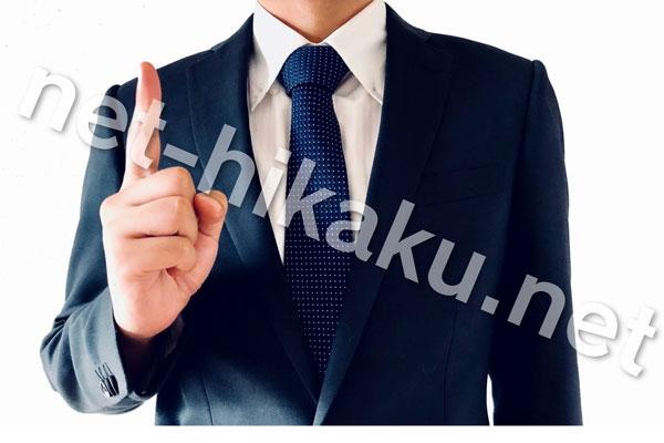 1を指すスーツの男性