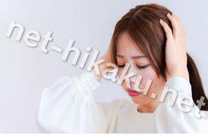 両手で頭を抱える白い服を着た女性
