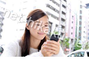 都会でスマホを見て笑顔な女性