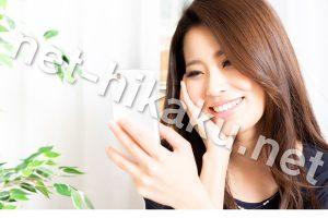 スマホを笑顔で見る女性