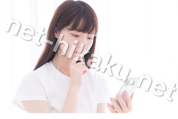iphoneを見て悩む白い服の女性