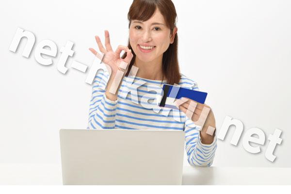 通帳を見てokサインをする女性